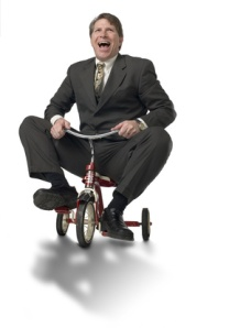 Executive riding child's tricycle