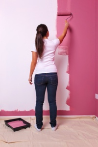 Woman painting a wall rear view