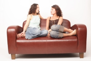 young women sitting on sofa and chating