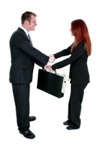 business man and woman shaking hands over briefcas